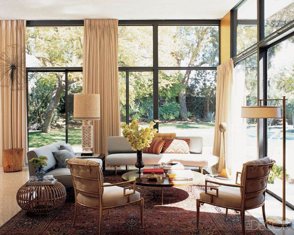A pair of 1948 Edward Wormley sofas for Dunbar upholstered in a Scalamandré linen, vintage armchairs, and a 1956 Richard Neutra cocktail table in the living room; the von Nessen floor lamp was purchased at auction, and the 1920s Persian rug is from ABC Carpet & Home