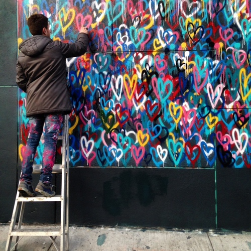 """James Goldcrown painting the """"Love Wall."""""""