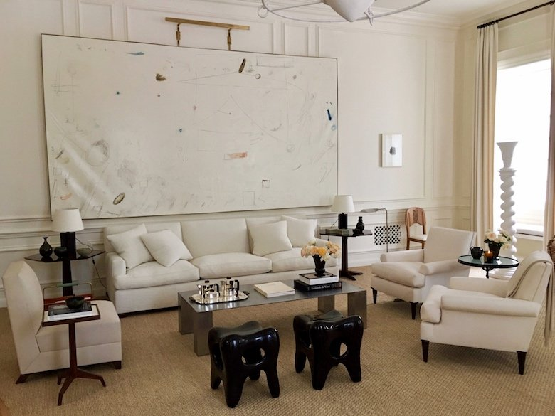Alyssa Kapito's all white living room for Holiday House NYC 2017 features a large painting by William McClure