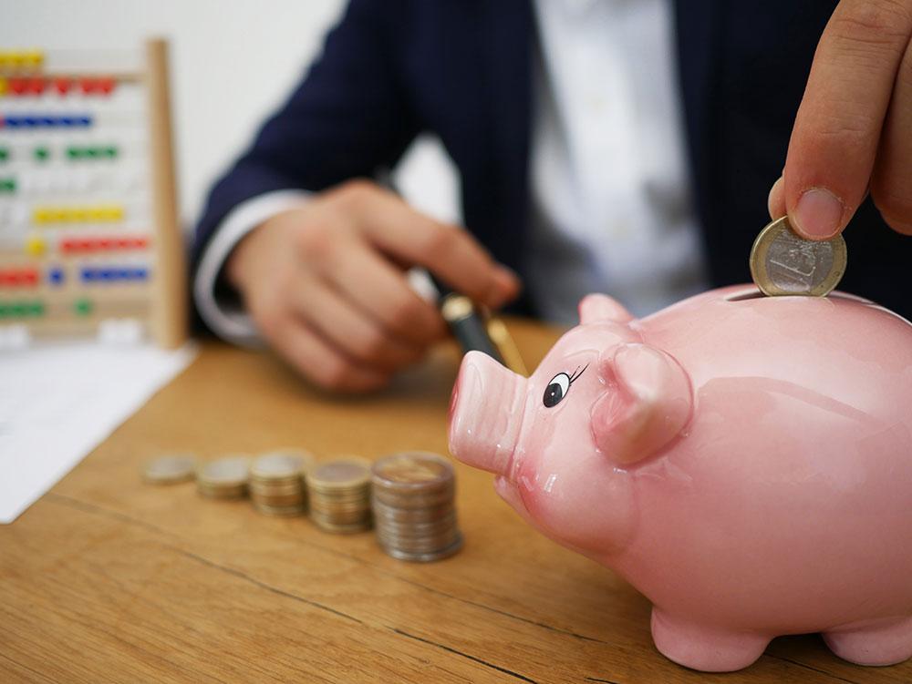 putting-money-into-piggy-bank.jpg