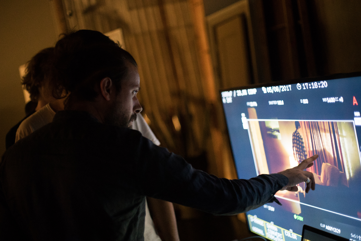 G.C.I. teacher explains lighting techniques to a student using a reference monitor on-set