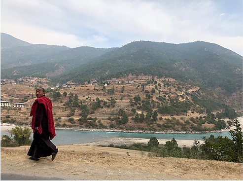A monk walking along a river in Bhutan.png