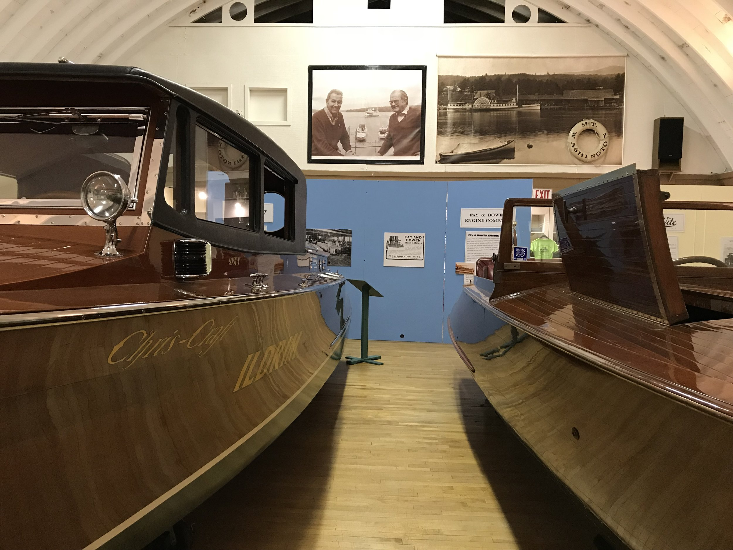 Two beautiful wooden boats on display.