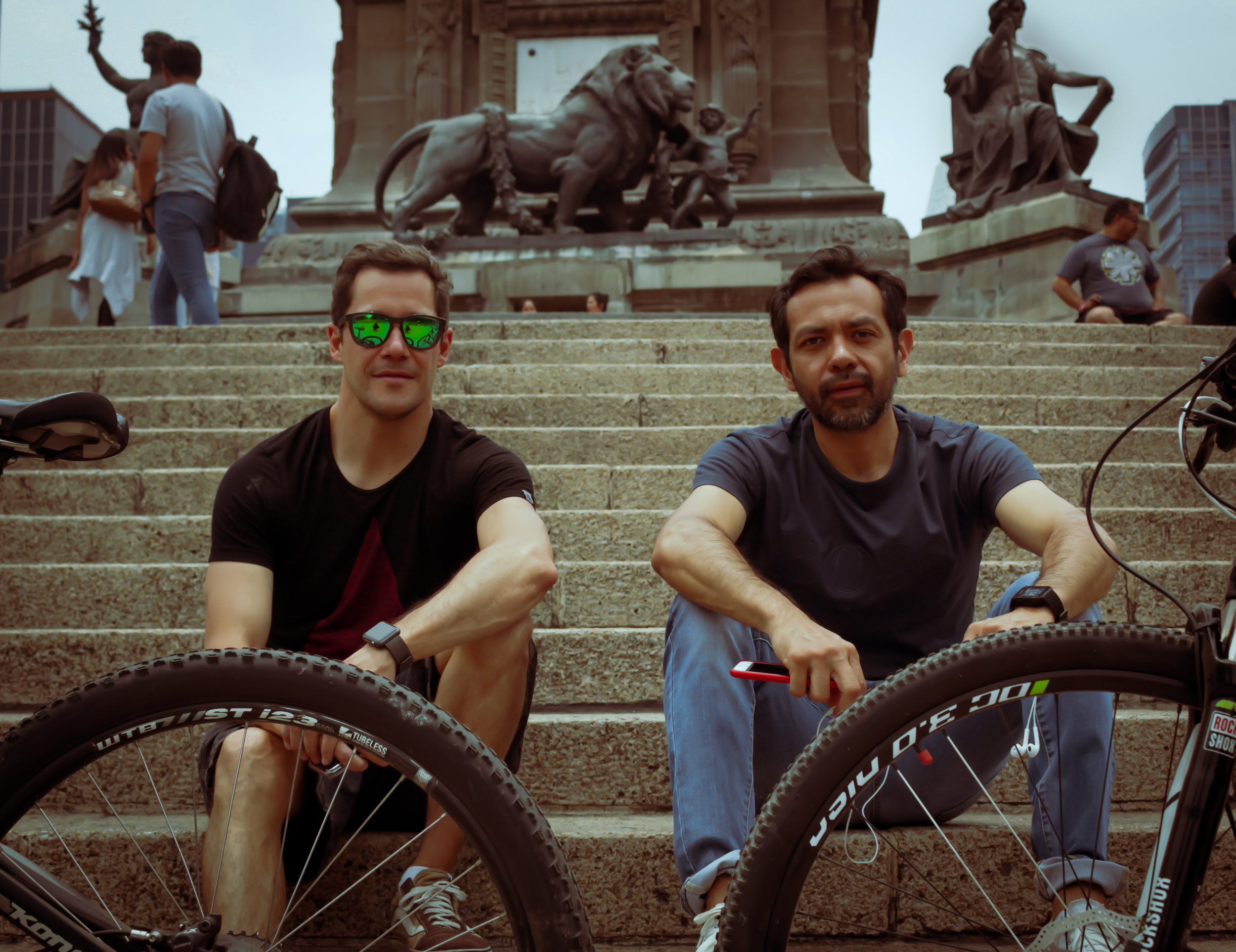 """José & Luís - I saw these two sitting on the steps leading to the the Angél de la Independencia, the most recognizable figure in the city. José has lived in Mexico City for nine years, but is from Spain (easily deduced by his still thick Spanish accent). Luís is a city native. They assure me I've come to ciclovía on the right day, as the last Sunday of the month is the most attended with 52km streets closed to cars (according to José).I ask how often they use their bikes.:José: """"(In Spanish) Minimum, at least once a week. I like riding for sport, exercise. It's a good way to hang out with friends.""""Luís agrees: """"(In Spanish) Yea I just use it for fun"""".José continues: """"It's good to see the city (ciclovía) without traffic, only for bikers. Its safer."""