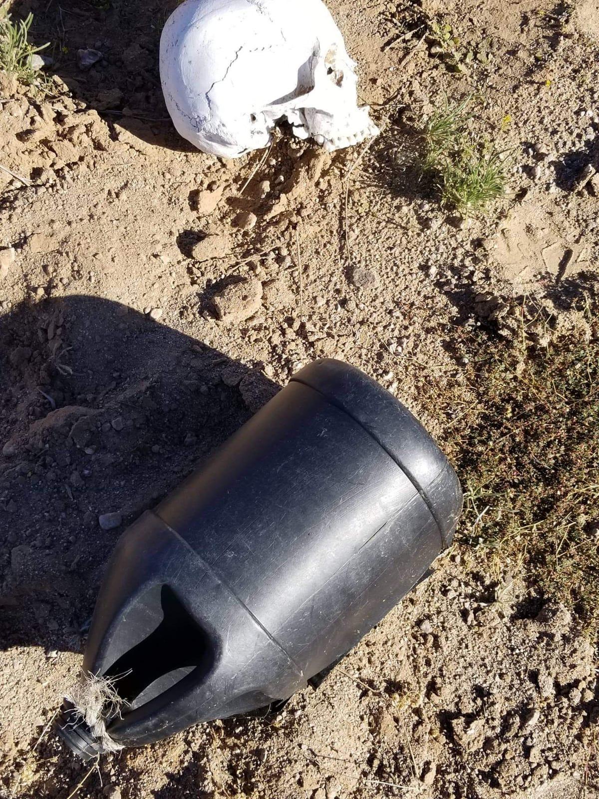 Imagen captura un bote de agua y un cráneo encontrados durante una búsqueda.