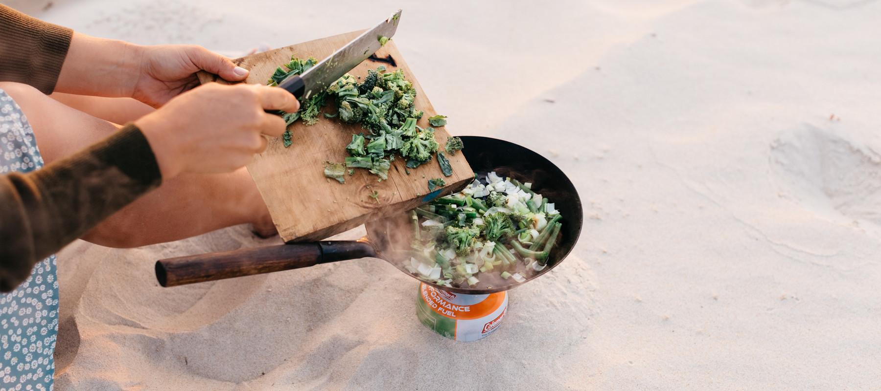 9ca5e6321b58c4891ae55375c1df05910f1f872a_recipe-food-fried-greens-smoked-bacon-eggs-beach-cooking-cutting-prep.jpg