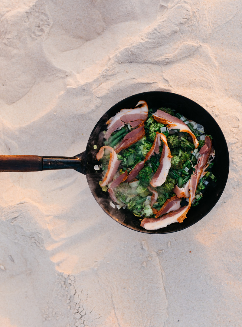 4f0a43e5fc5a194184e10b460cda51cab8bec3ac_recipe-food-fried-greens-smoked-bacon-eggs-beach-cooking-aerial-view.jpg