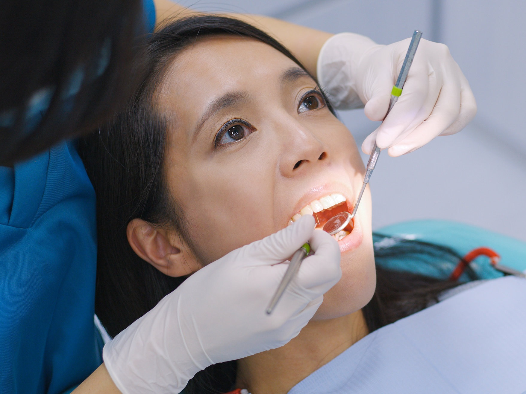 Oral Hygienist Cleaning Woman's Teeth at Total Health.