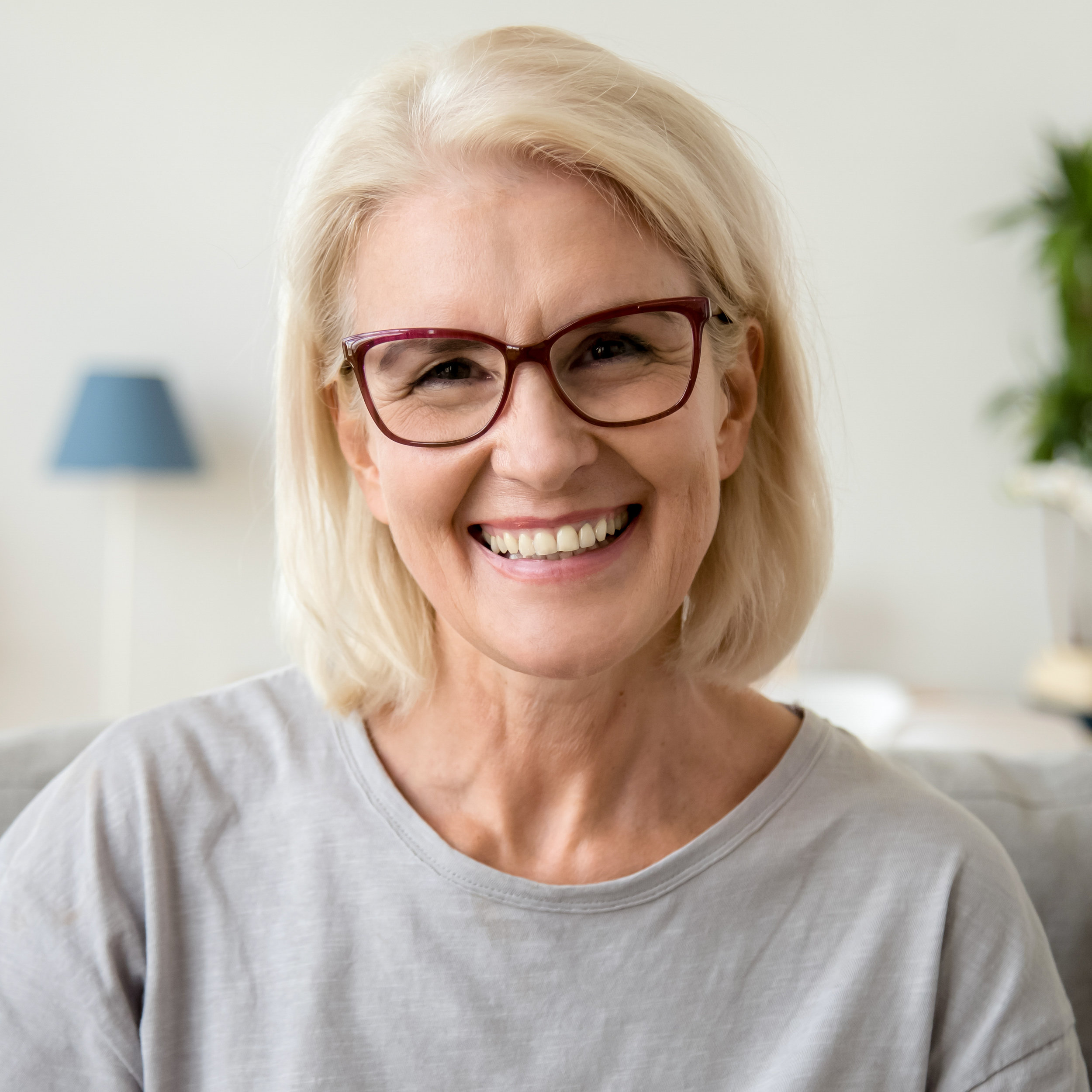 Older Woman Smiling with nice teeth after going to Total Health Dental Care.