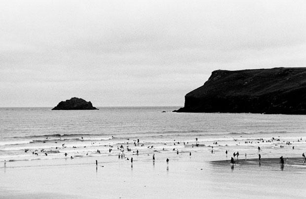 TINY SURFERS IN THE CELTIC SEA, POLZEATH, ENGLAND, 2010 ARCHIVAL PIGMENT PRINT