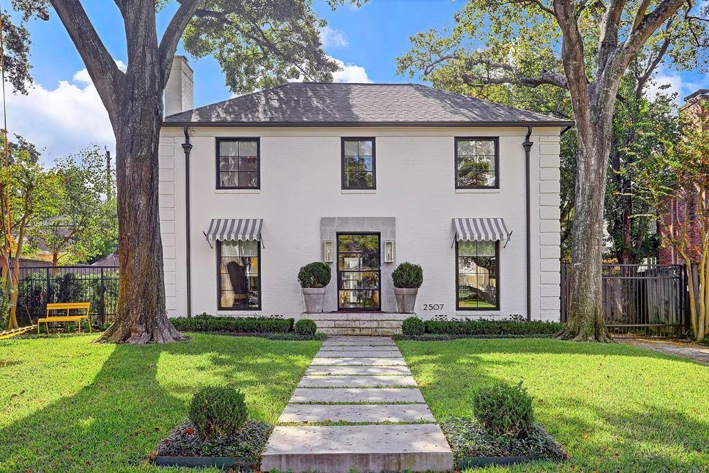 White paint. Steel glass front door and windows. Stone surround. Trendy stepping stones.  AND awnings! Another reno trend.  Seriously – is this the same house? Incredibly it is.