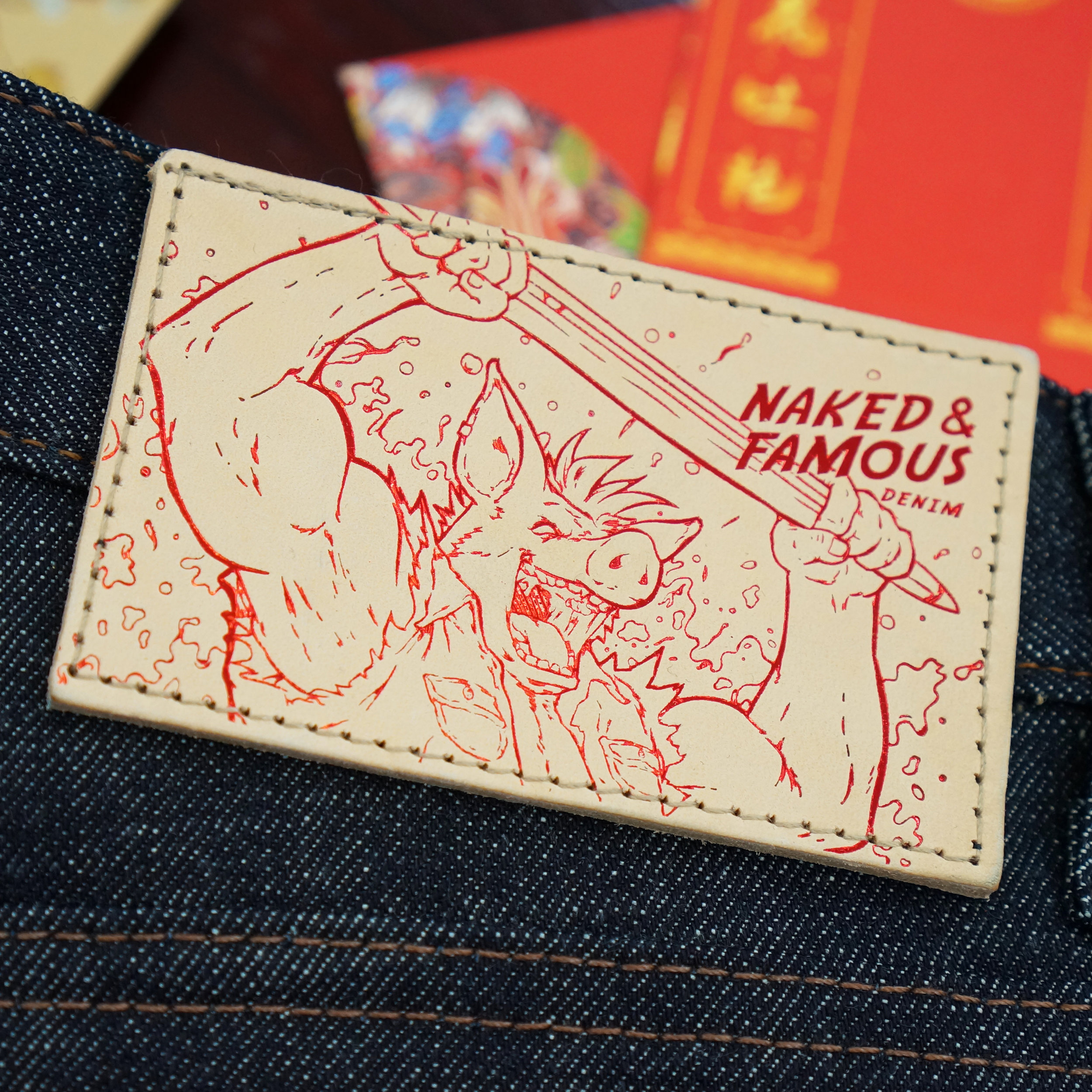 Natural vegetable tan leather patch with red metallic foil print of the Earth Pig holding a shuttle
