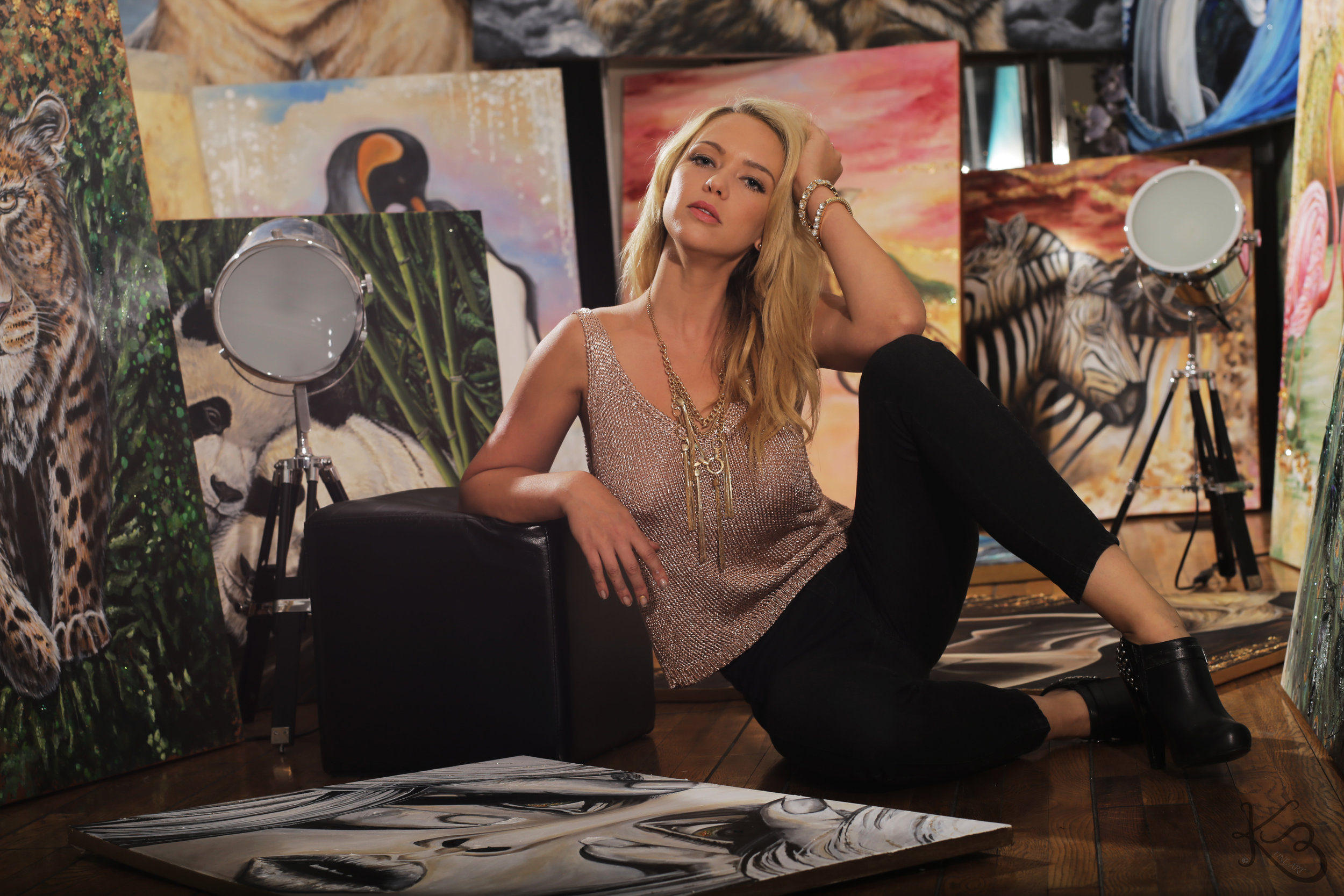 Karin on the floor surrounded by her art