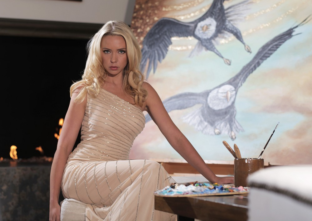 Karin in a gold dress with her Bald Eagle painting