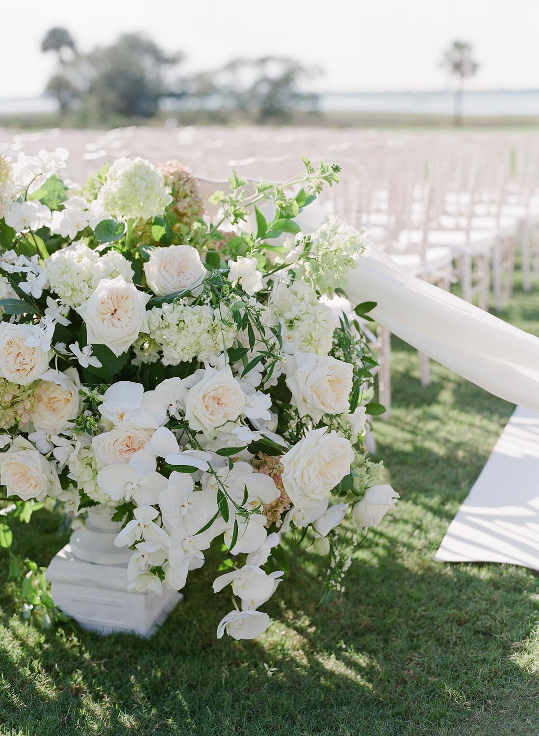 Large lush white ceremony flowers with roses and orchids. Wedding planning and design by A Charleston Bride.