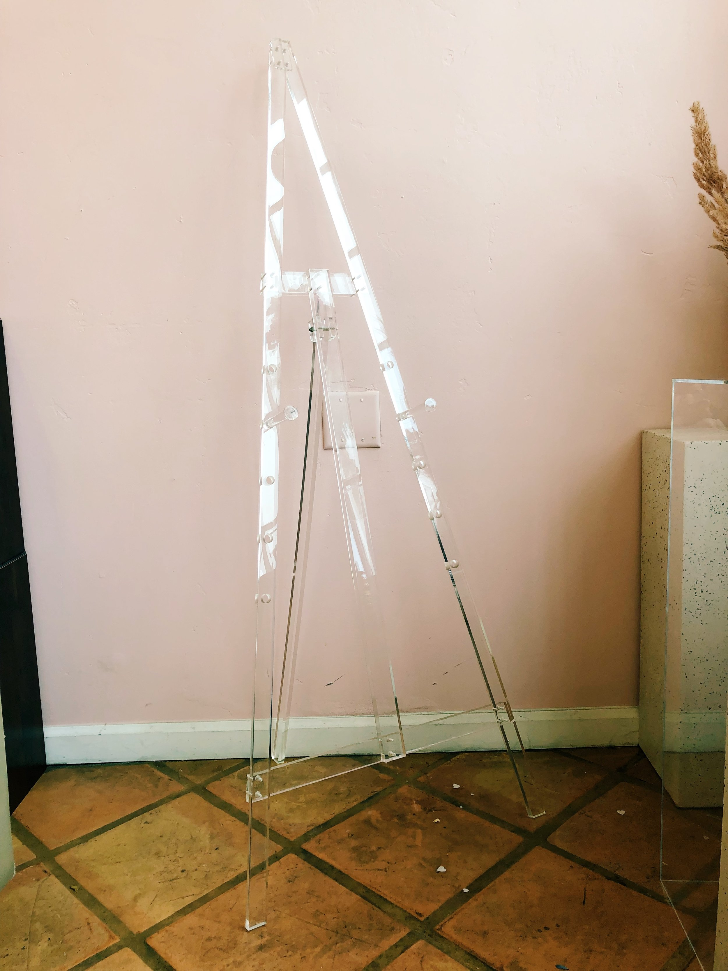 "Acrylic Easel - A modern acrylic easel with adjustable pulls for any sign, big or small. 60""h x 32""w."