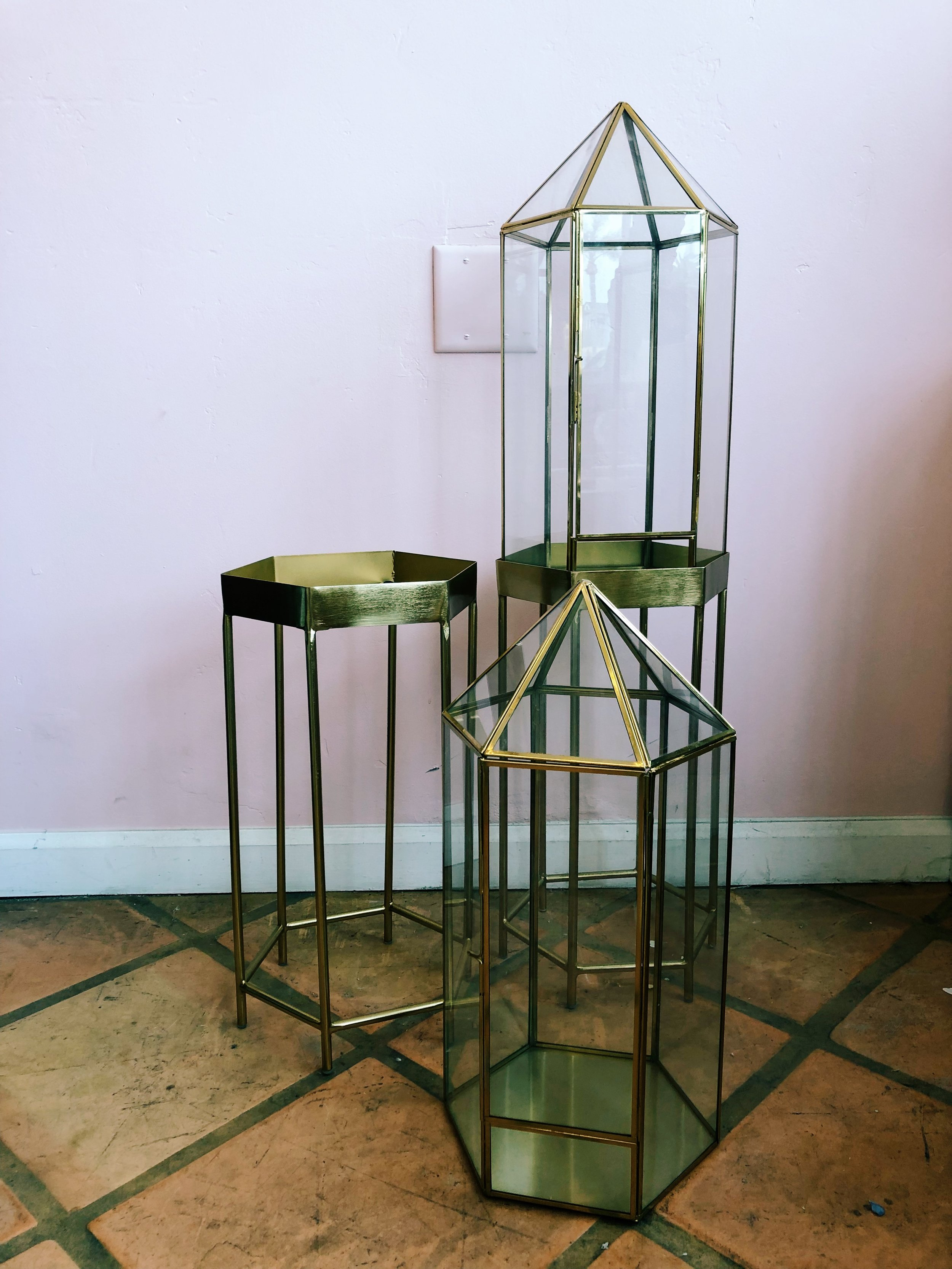 "Gold Geometric Lanterns - Gold Geometric Lanterns with stand. Swing door on lantern to add candles/floral decor and can be removed from stand for easy repurposing. Two available. Together 37""h x 10""w x 10""d, stands only 10"" x 10"" x 18""."