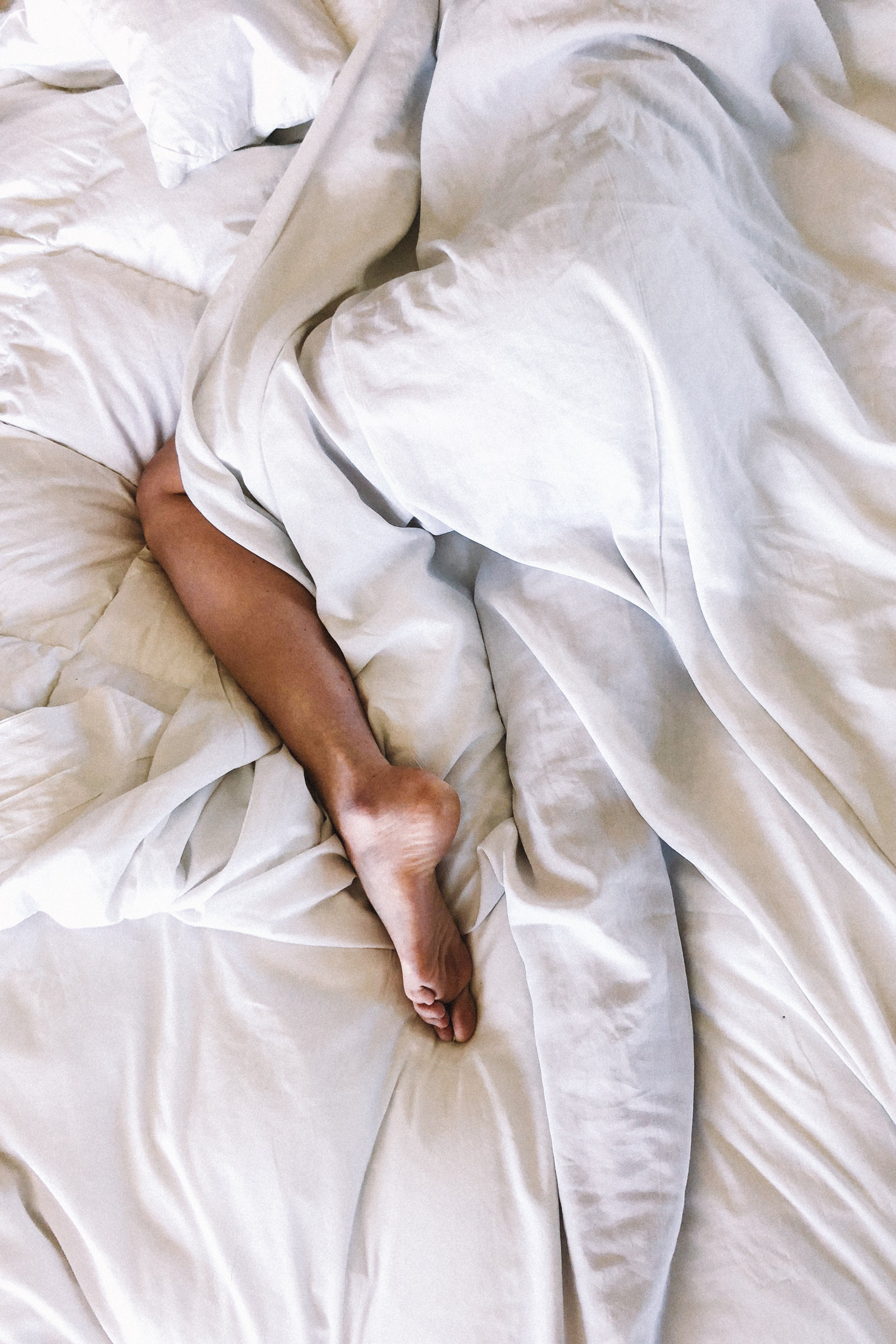 Person laying in bed, white sheets and quilt with one leg out from under the covers.