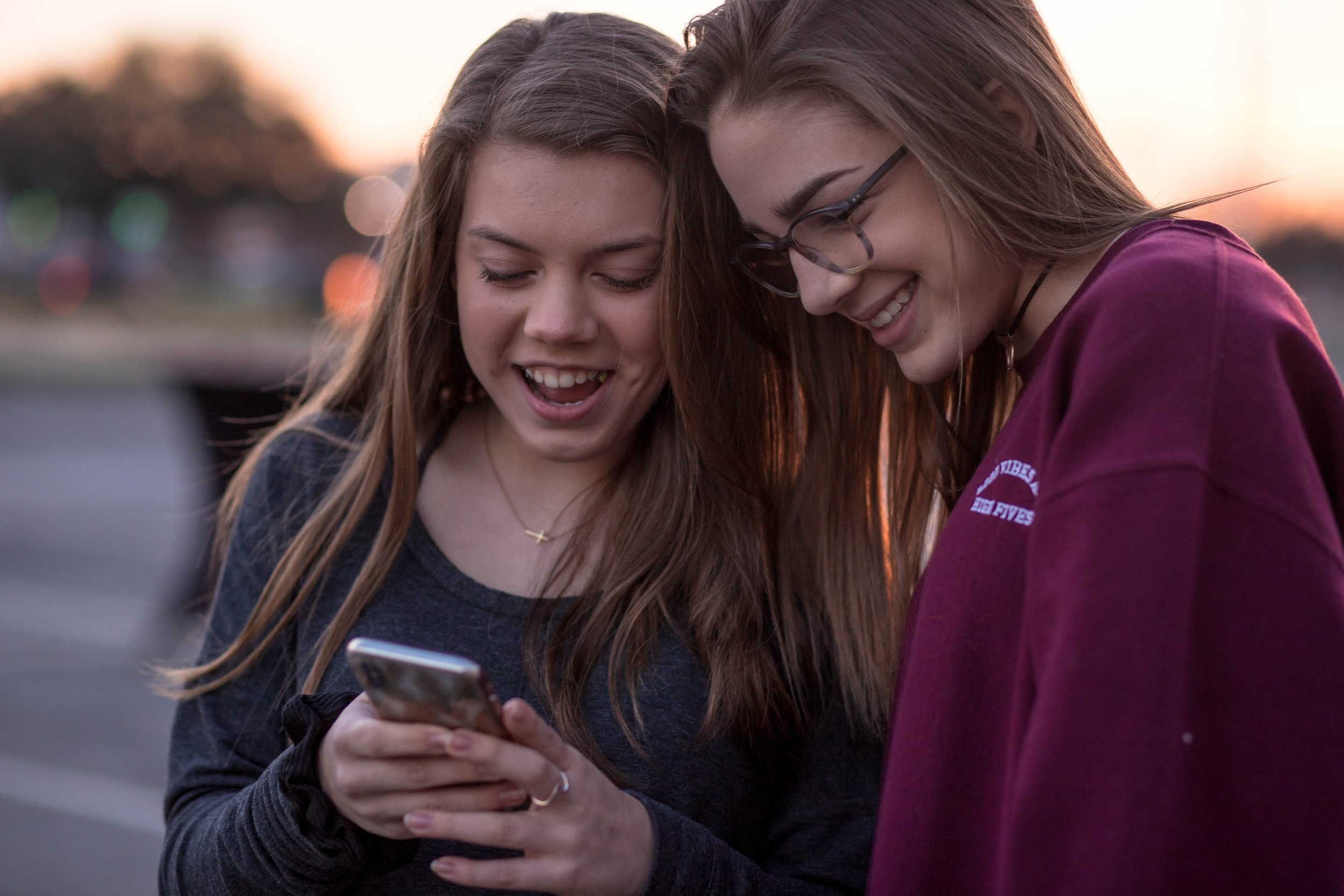 Two teenage girls looking at a mobile phone.