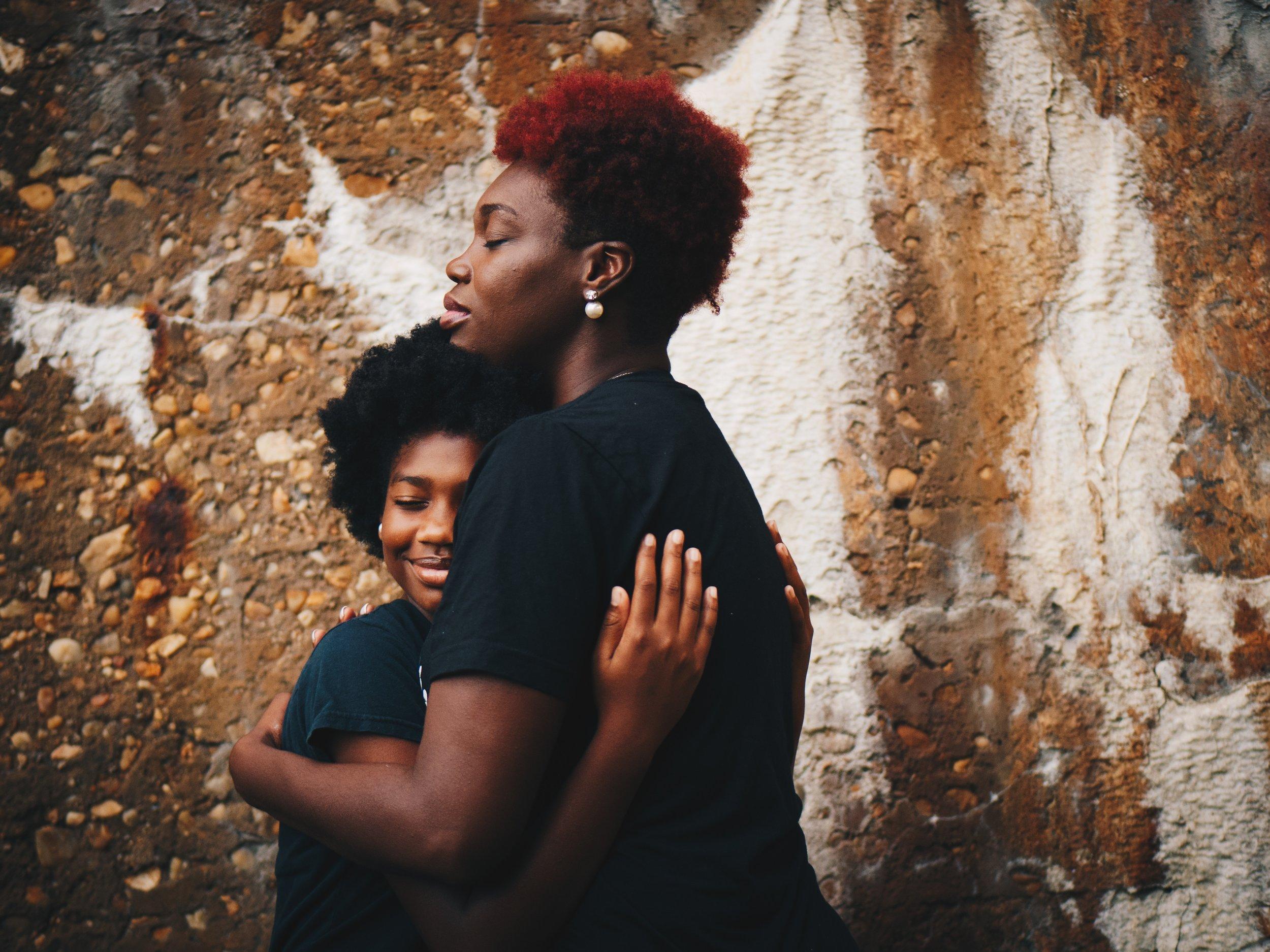 Mother hugging teenager.