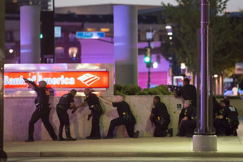 File photo from July 7, 2016 as Dallas police take up positions along a wall at the corner of Lamar at Main streets in downtown Dallas after shots were fired during a Black Lives Matter rally. Jorge Barrientos (third from left) gets his hand wrapped by a fellow officer. (Smiley N. Pool/Staff Photographer)