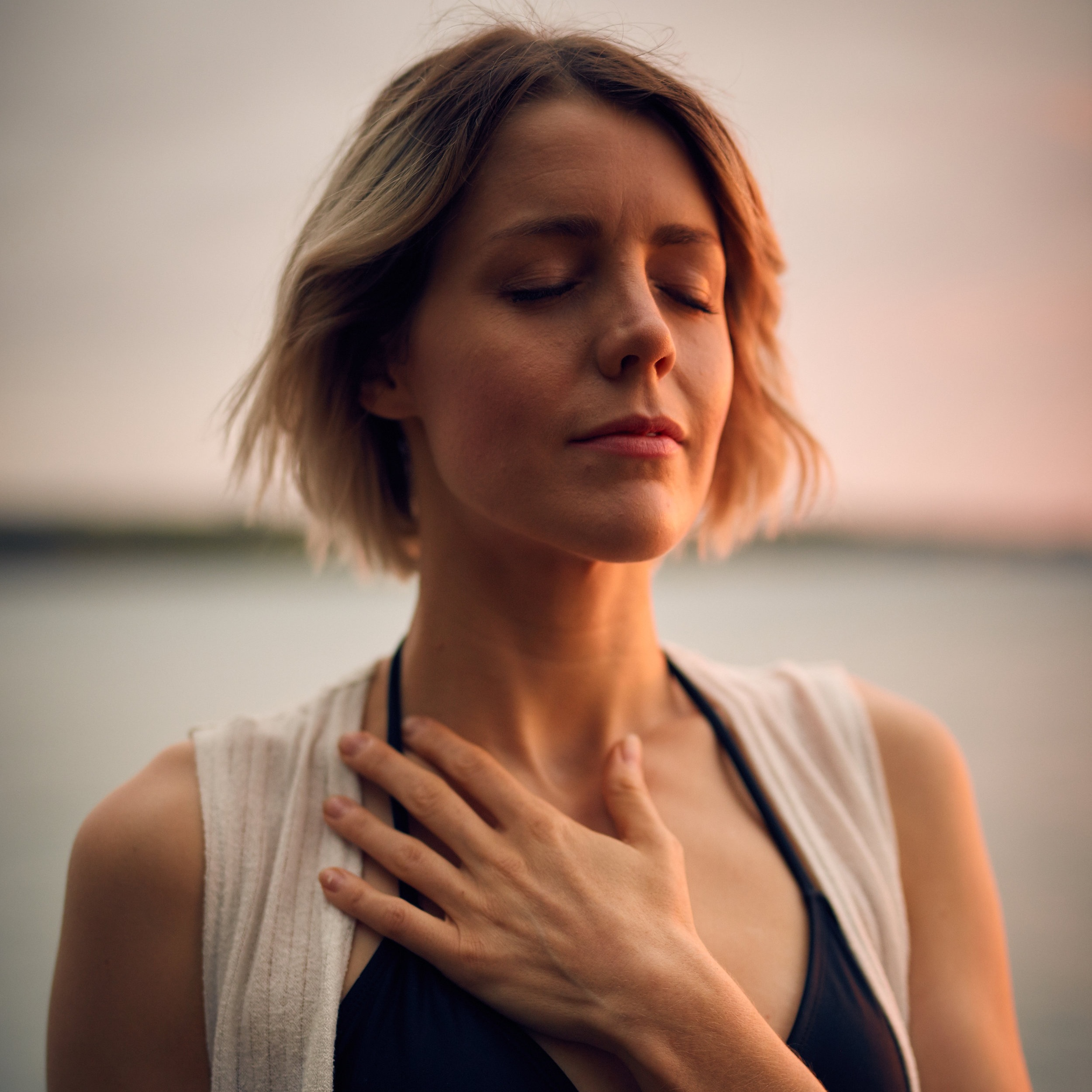 Woman with hand on her chest meditating. Energy healing Charlotte, NC