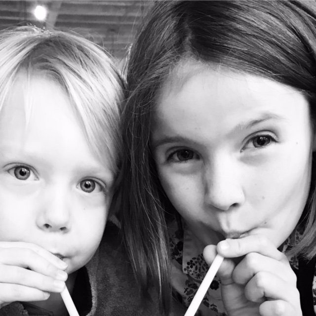Sibling sips out of paper straws