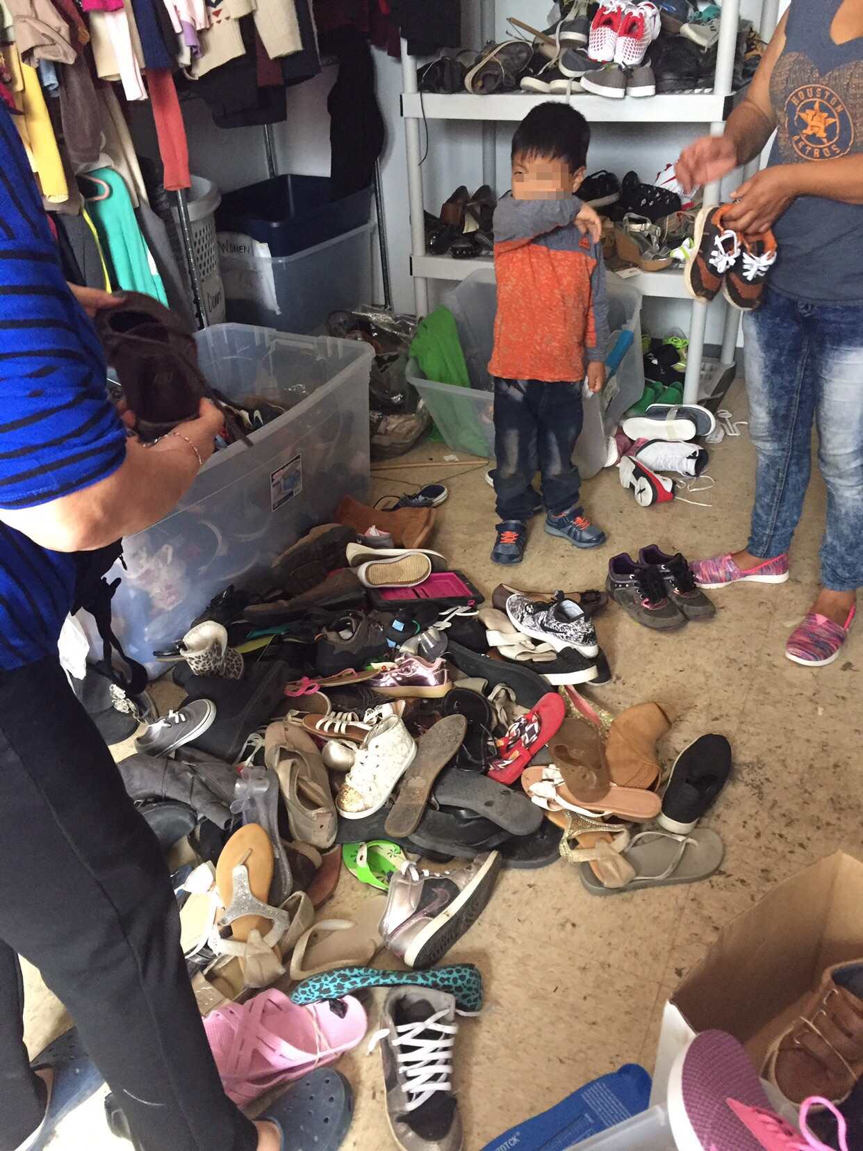"""Pam and I in the """"shoe room"""" at Catholic Charities in McAllen, TX, finding shoes for refugees who had just been released from detention. The room had been raided the previous night."""