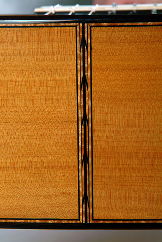 Endstrip detail showing flame maple herringbone marquetry