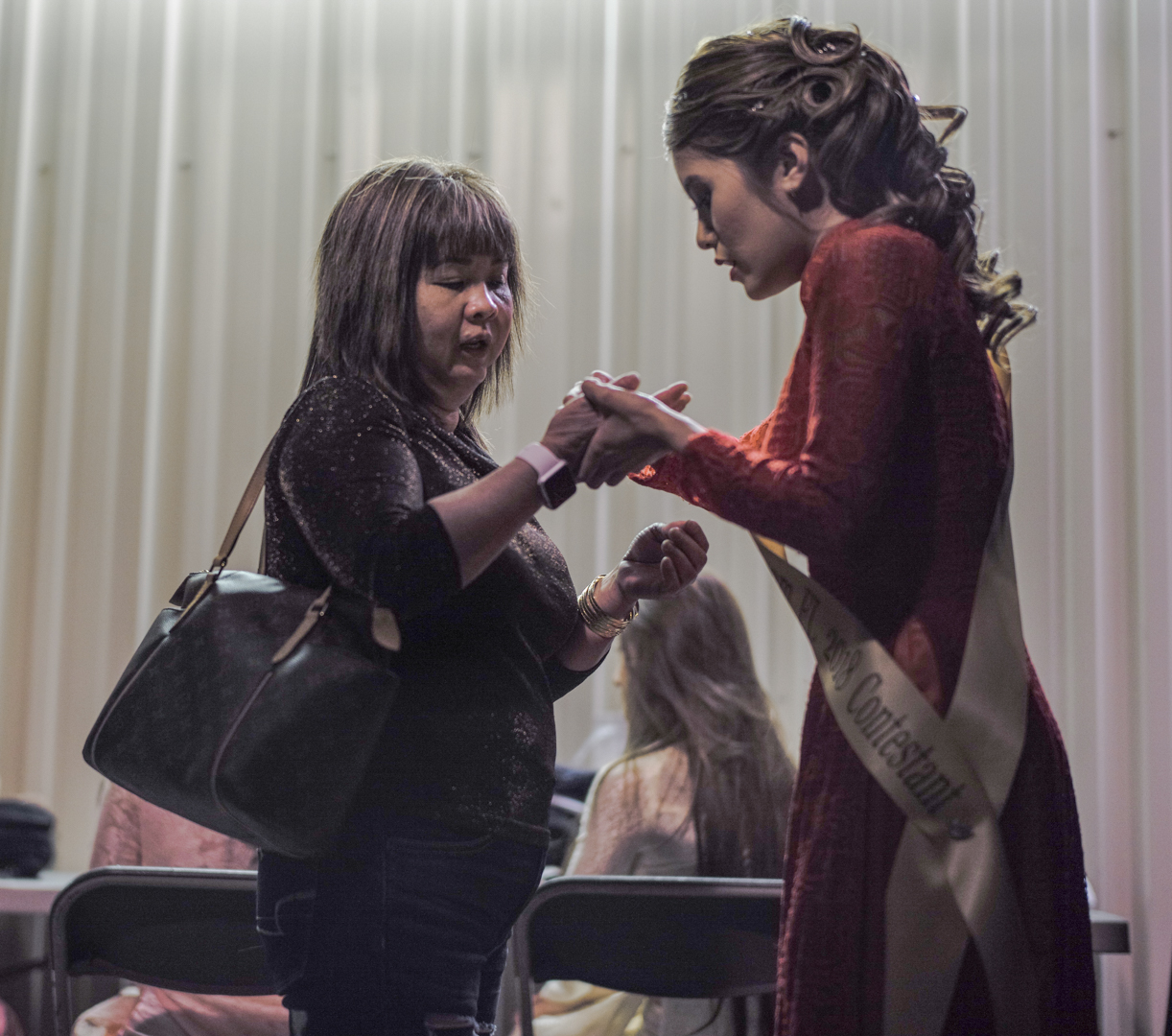 Nhung Hồng Phan shares a moment of prayer with her mother backstage moments before the show began.