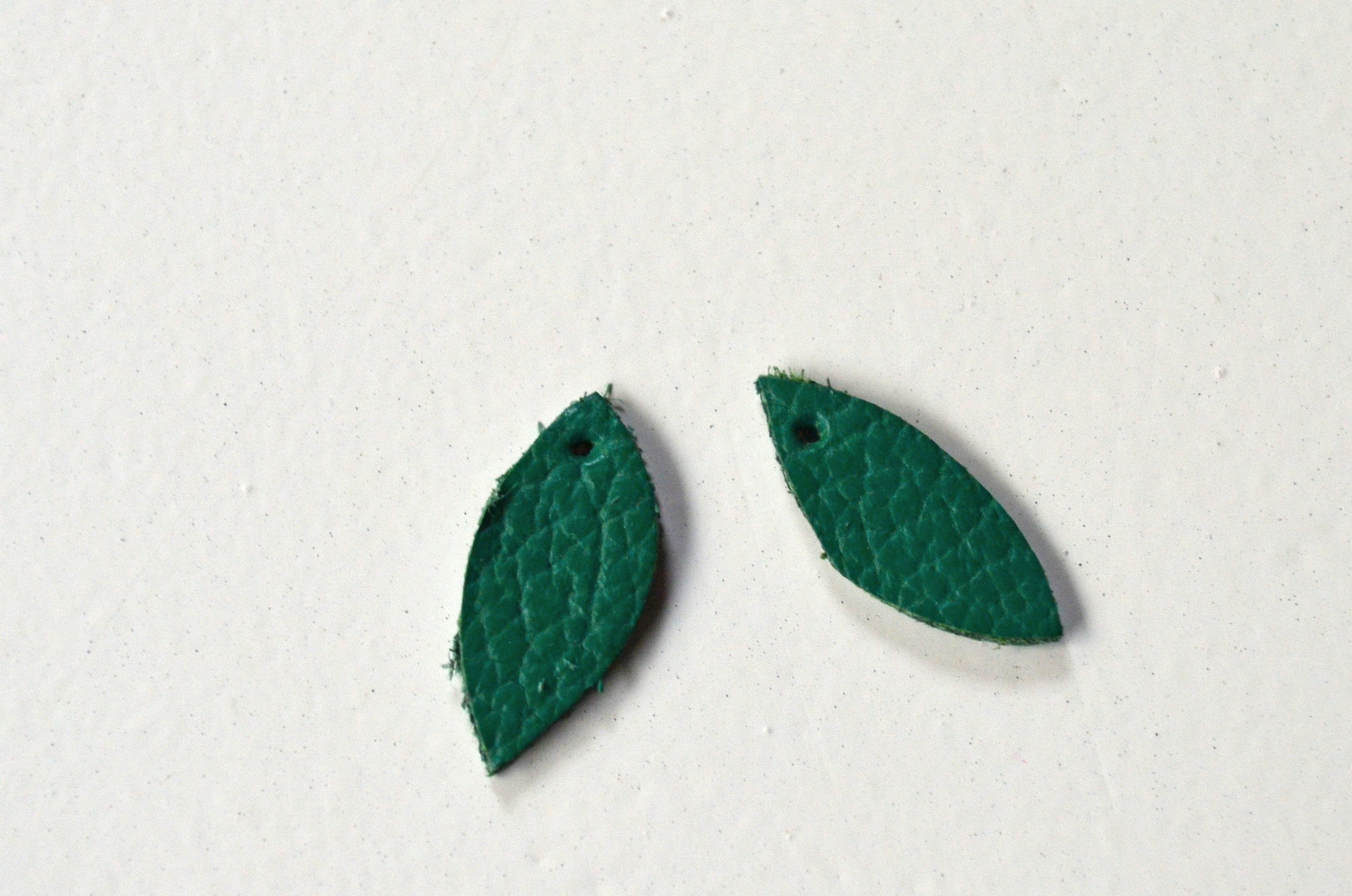 "From the leather cut two leaf shapes about ¾"" in length. Using an awl (a larger safety pin may also work) poke a hole in each leaf large enough to attach a jump ring."