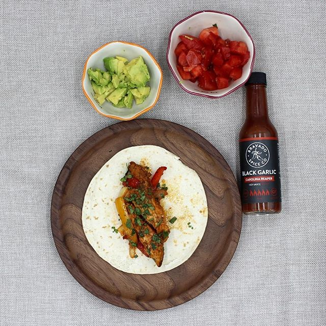 Here's a quick-to-make dinner idea for #foodfriday ... Fajitas! This was all roasted on one sheet pan. All 4 Bairds, big and little, loved it. ⁣ ⁣ Adam and I like to add a 🌶️ kick to just about anything, so hot sauce is a must in our house. In fact we currently have 8 different hot sauces in our fridge! ⁣ ⁣ Pictured is @bravadospice Black Garlic Carolina Reaper hot sauce. It's not for the faint of heart, but if you love some heat we definitely recommend it! It was featured on Hot Ones. An awesome YouTube show where celebrities attempt to eat 10 hot wings rated from mild to 🔥🔥🔥🔥🔥🥵. There's something great about watching them sweat it out. ⁣  @seanseaevans @firstwefeast