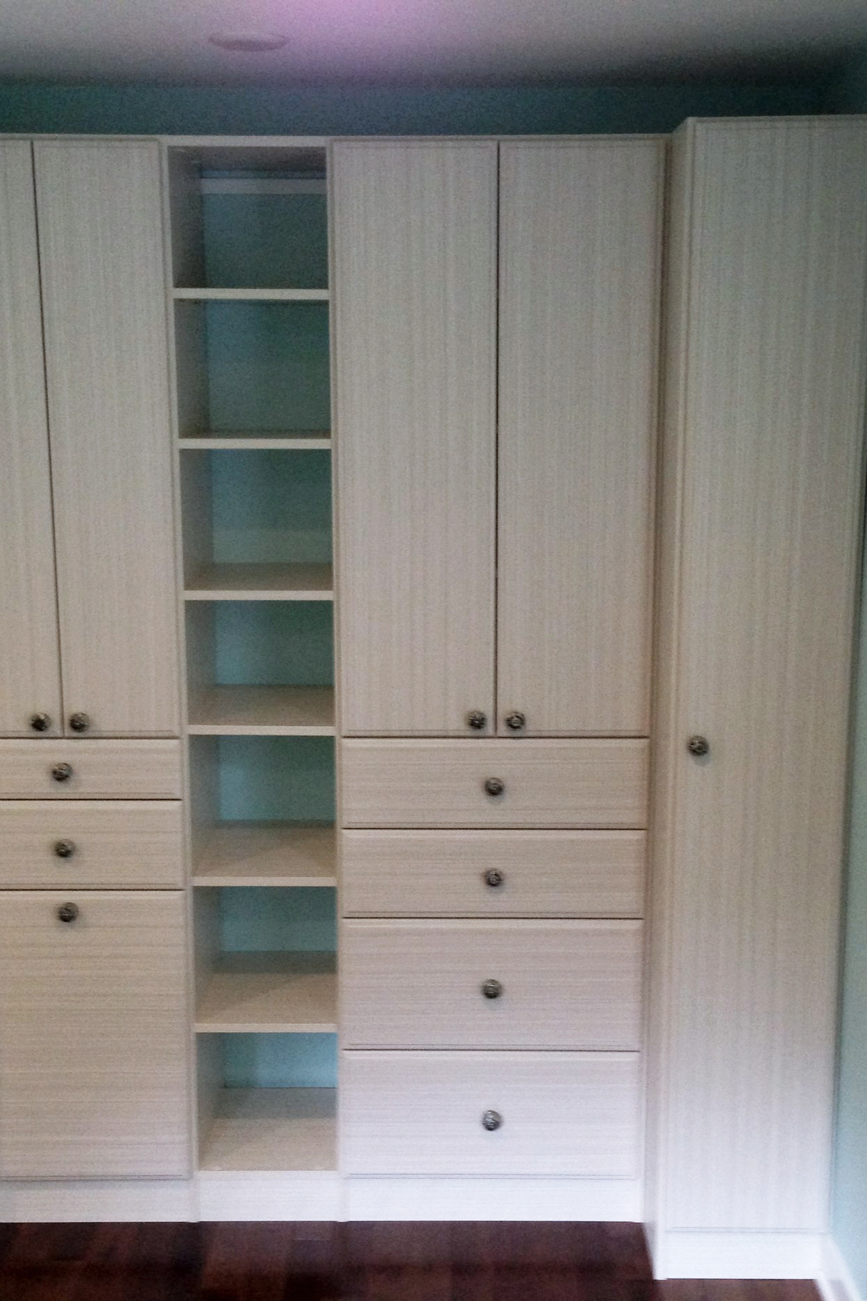 White chocolate textured finish wardrobe wall system with shelving, cabinets and drawers.