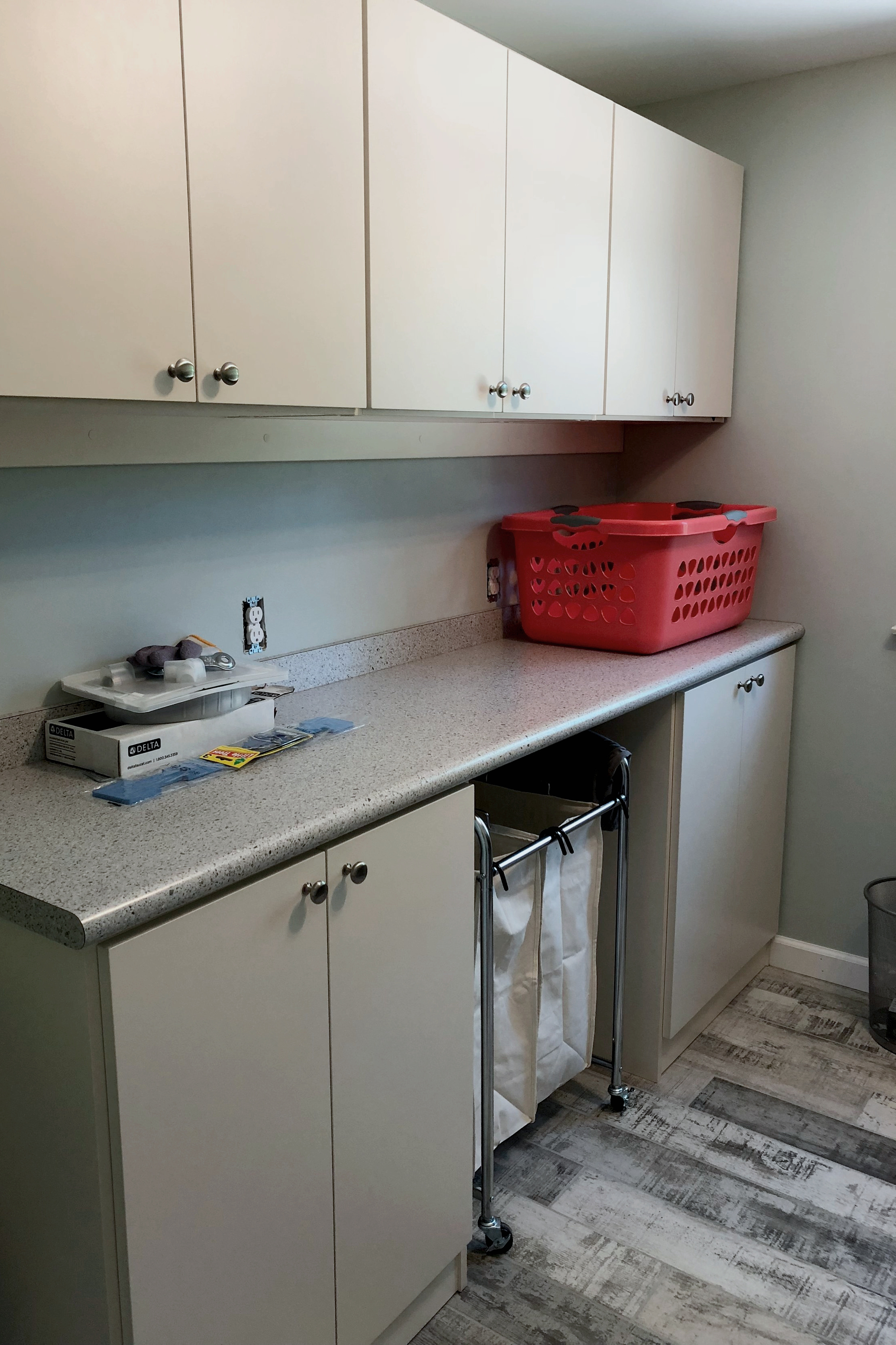 Laundry room with antique white upper cabinets, a folding surface with a Formica top and and lower cabinets in grey.