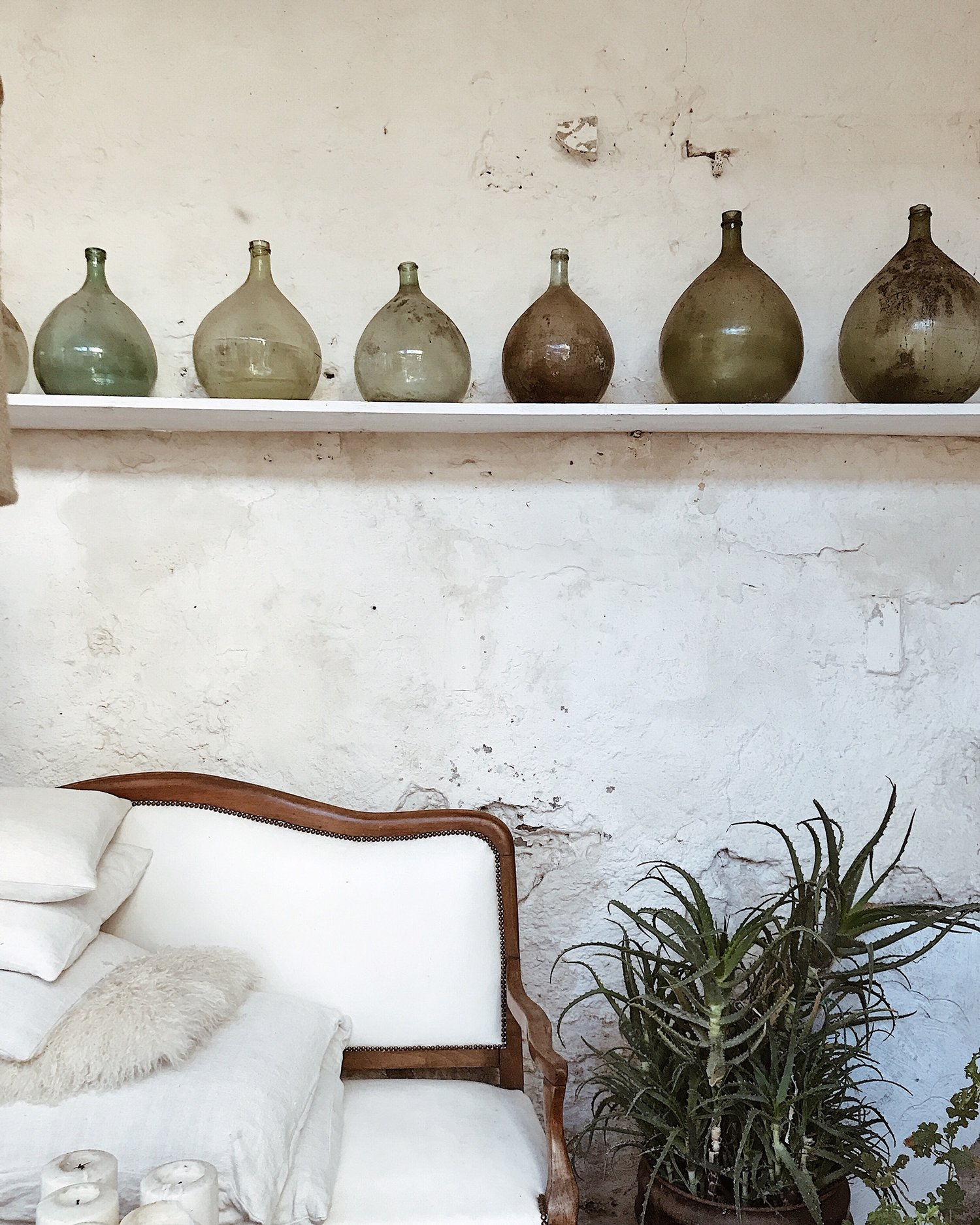 camellas-lloret-maison-d'hotes-greenhouse-couch-white-bottles.jpg
