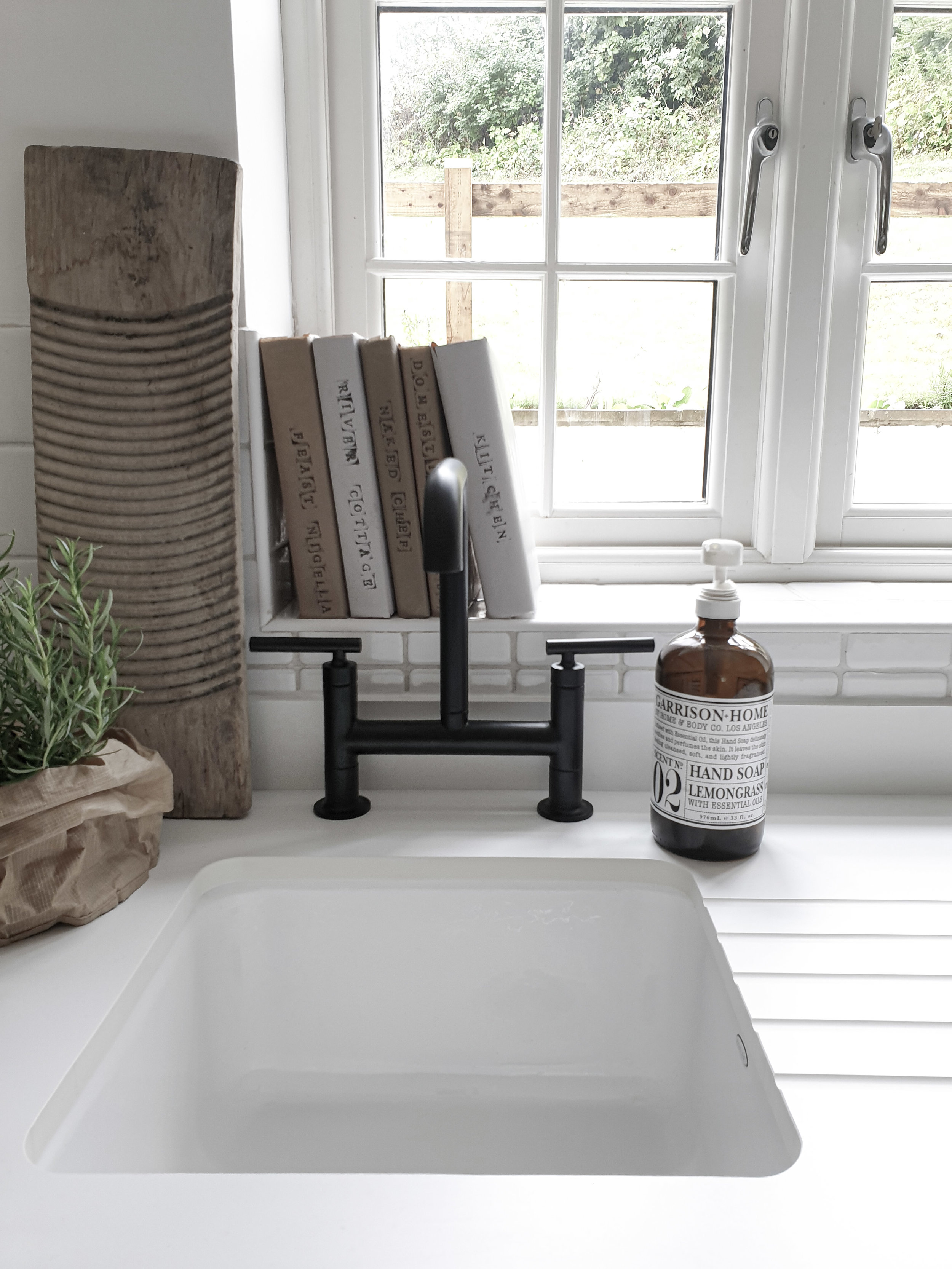 Here the old washboard used as a pot stand provides texture and contrast next to the modern black tap by Kohler.