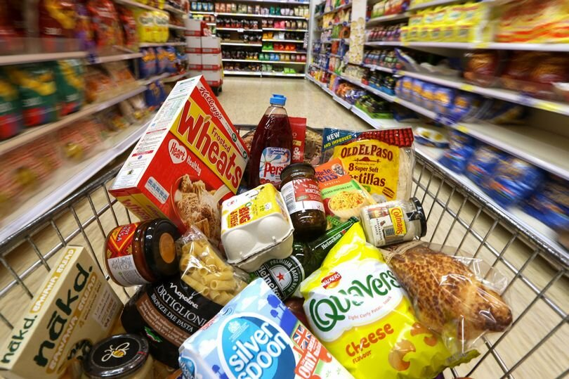 Groceries-in-a-shopping-trolley-move-through-a-food-aisle.jpg