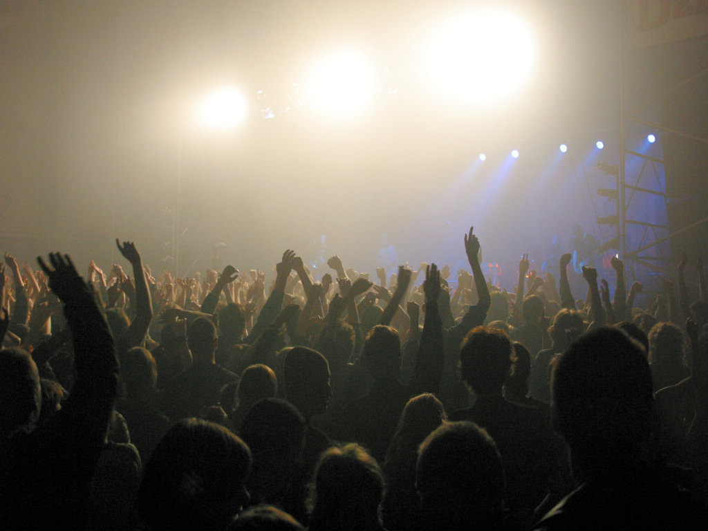 concert-crowd-hands-raised-bright-lights