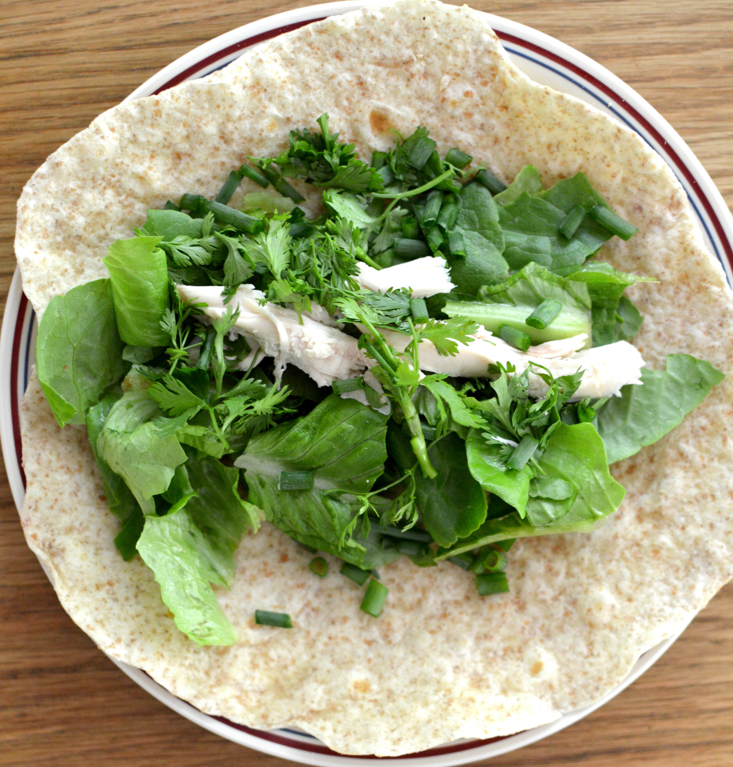 Homemade Spelt Flour Tortillas with lettuce, cilantro, green onions, chicken, and homemade dressing. We roll them up and eat them like a wrap.