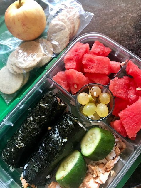 Homemade sushi w/ rice + salmon, zucchini, watermelon, grapes, rice crackers + apple. -