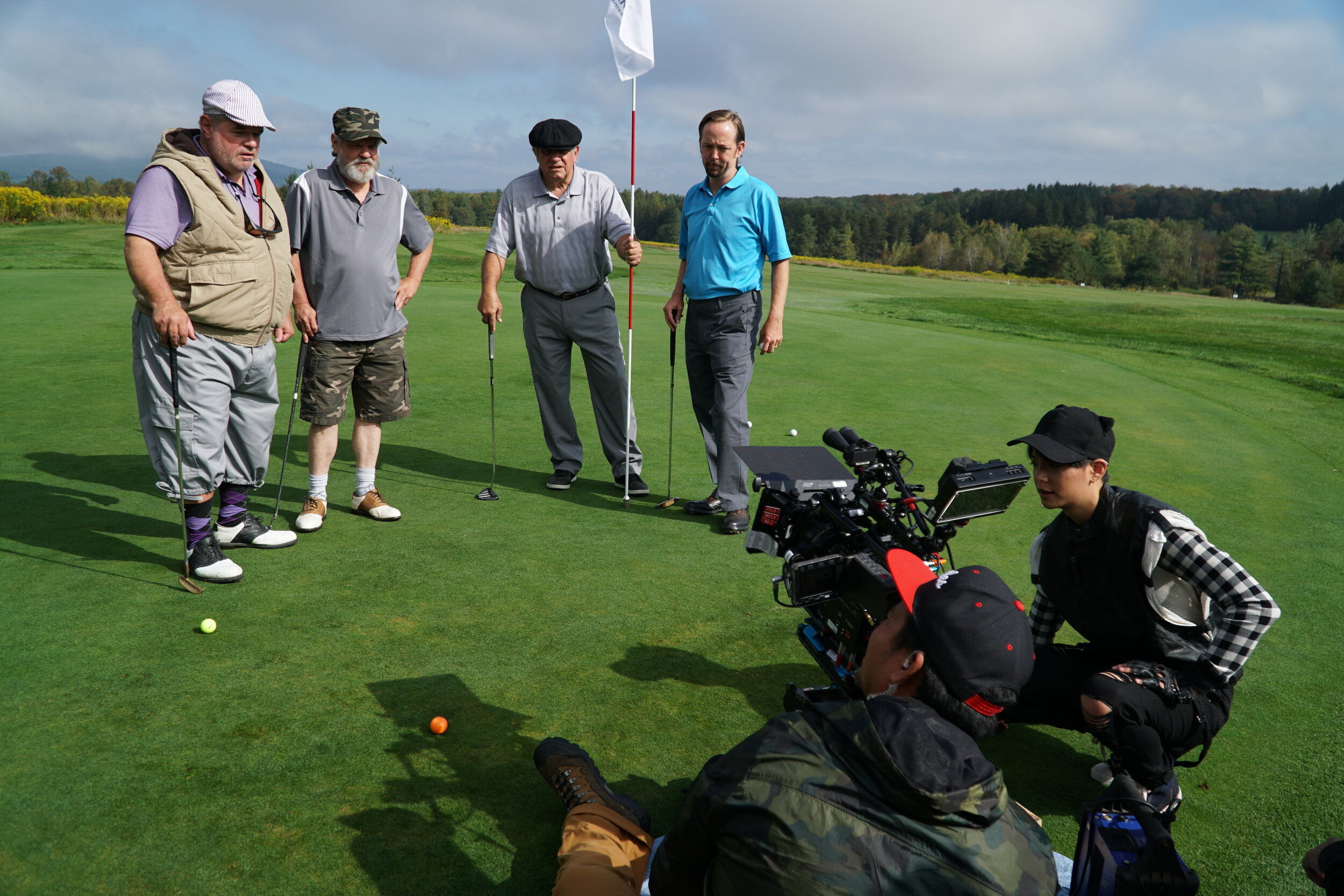 Director of Photographer, Leonidas Jaramillo, checks a shot with Amber Liu of the golf partners.