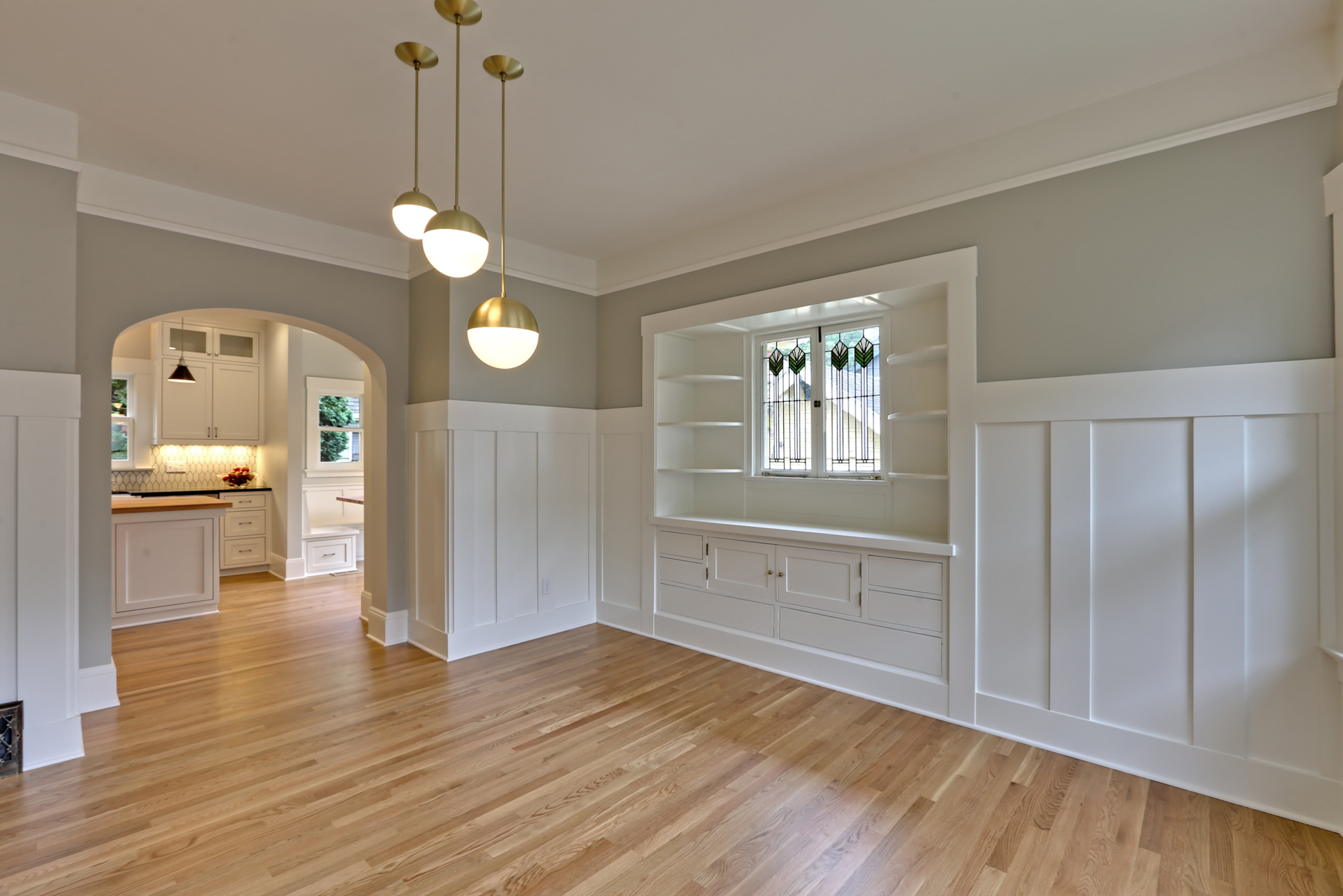 We redesigned the passageway from the dining room into the kitchen for better flow and to match the arches found elsewhere in the home. Fun light fixtures from Rejuvenation compliment the revitalized original cabinets and wainscoting; blending old and new really works on projects like this.
