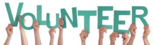 Many-Hands-Holding-the-red-Letters-Volunteer-Isolated-1024x300-300x88.jpg