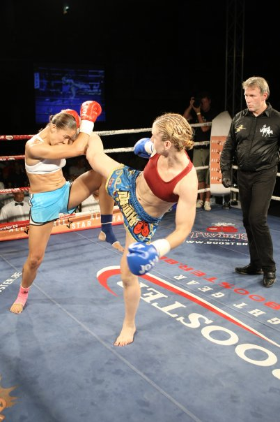 Coach Casey landing a strong middle kick during one of her professional fights.