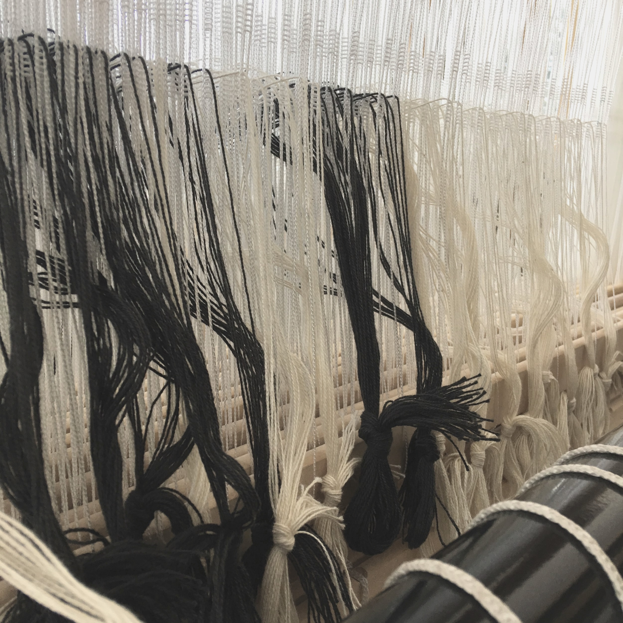 Threading the Heddles…. - Each end feeds through a heddle assigned to a shaft. The amount of ends range but our towels can have as many as 600 ends. That's 600 heddles threaded for one project.