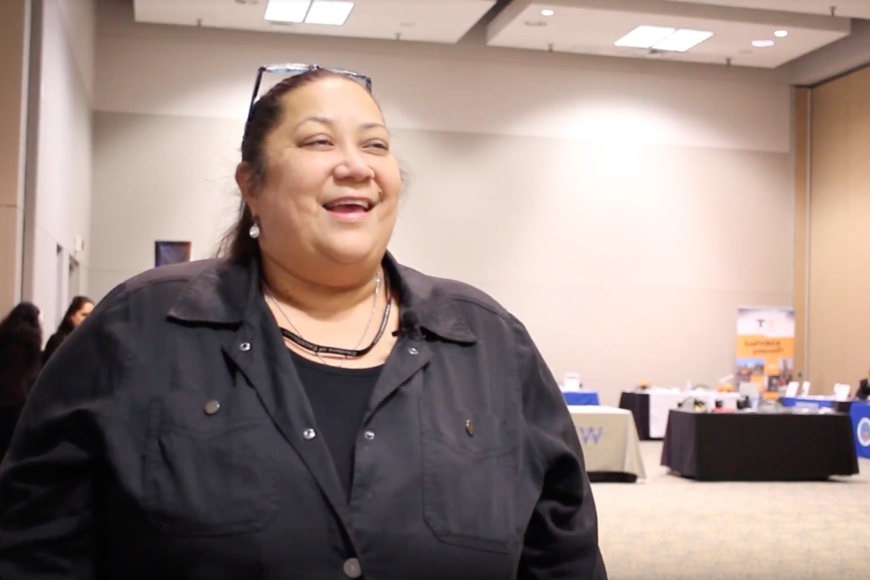 Video still of smiling woman in black shirt.