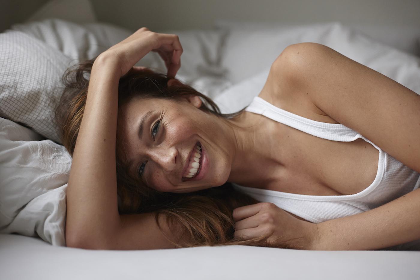 GettyImages-smiling-woman-bed-Philipp-Nemenz.jpg