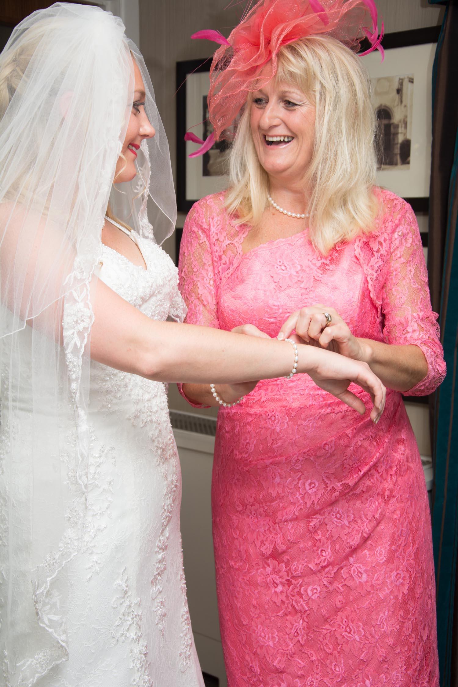 brides mother smiling while fastening brides bracelet