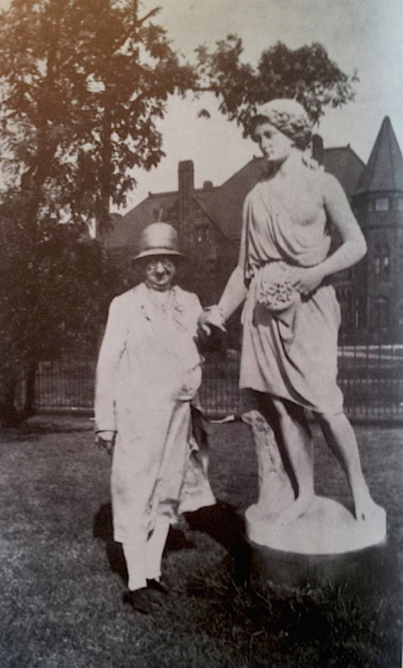 Ella Grant Wilson was a florist and historian for the avenue. She poses here with a sculpture in front of the Everett mansion.