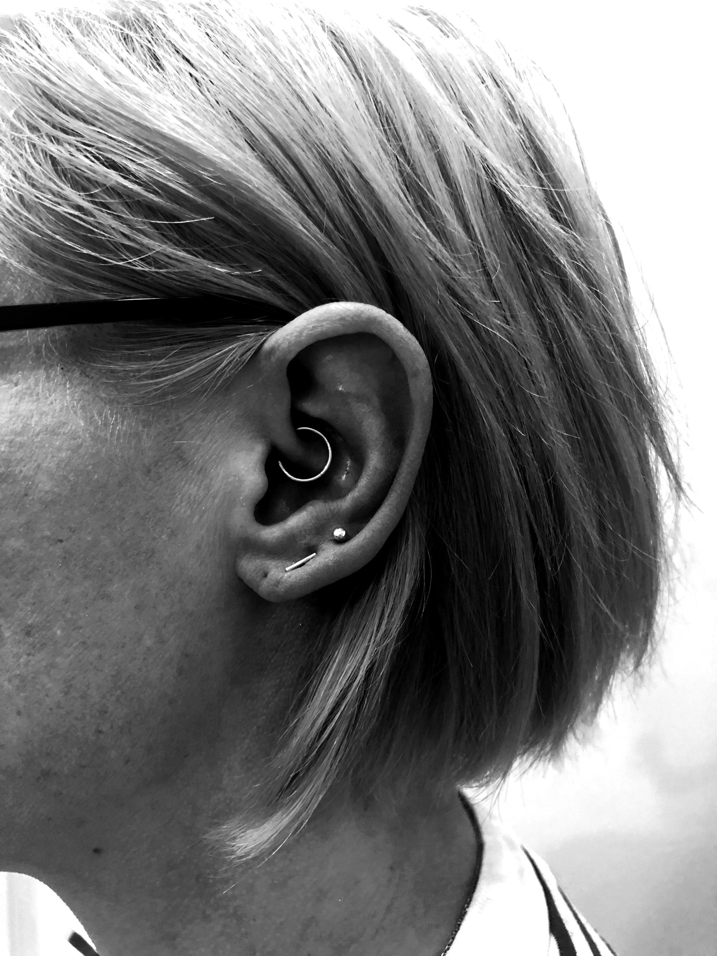 Beautiful Daith piercing alongside existing lobe piercings